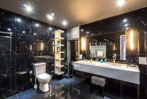 חדר אמבטיה מעוצב בצבעים כהים עם מראה